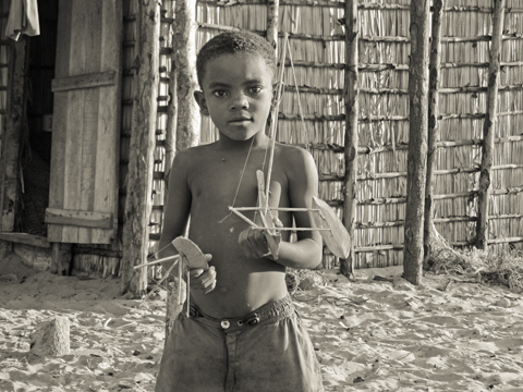 Boy in Madagascar with wooden boats
