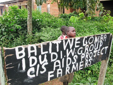 Children behind AIDS Project sign in Uganda