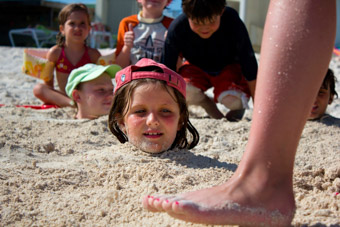 girl buried up to neck in the sand at beach