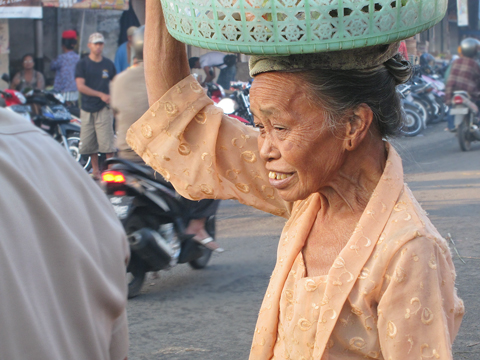 woman carrying basket of fruit Bali Indonesia