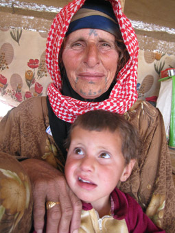 Bedouin woman with facial tattoos holding baby