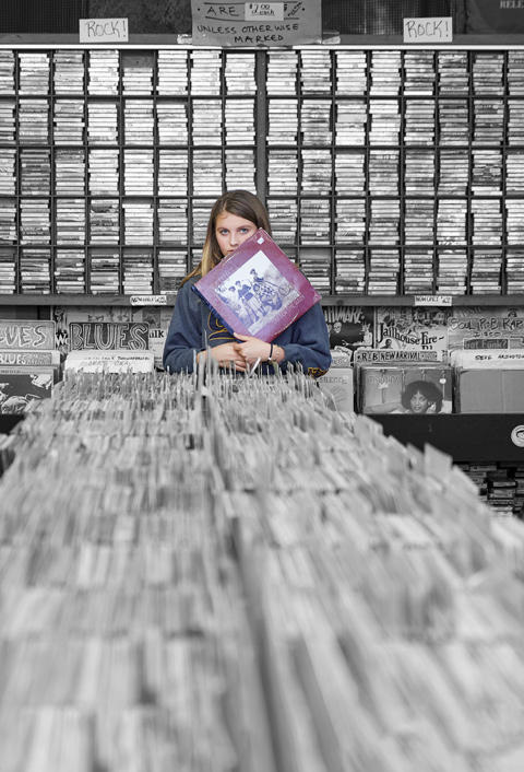 Teenage girl in record shop holding record