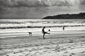 young man playing soccer on beach costa rica