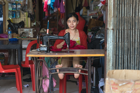 Woman tailor sewing outside her shop Siem Reap Cambodia